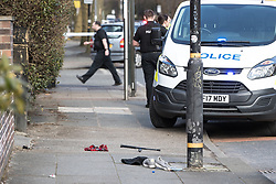 © Licensed to London News Pictures . 25/03/2018 . Manchester , UK . Police close off a section of Upper Chorlton Road in Chorlton-cum-Hardy following reports of a man armed with a sword . Clothes , used Tasers and a police baton lie scattered on the road and pavement following a reported struggle with a man , who was tasered at the scene . Photo credit : Joel Goodman/LNP