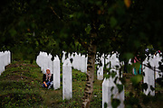 A grieving woman in the fields of the Potocari memorial for victims of the Srebrenica genocide.