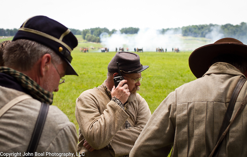 Kent Crutchfield, of Romance, Arkansas, listens on a walkie talkie to  ensure safety precautions, while playing the part of General Fry's Chief of Staff in the reenactment of Pickett's Charge during the Sesquicentennial Anniversary of the Battle of Gettysburg, Pennsylvania on Sunday, June 30, 2013.   John Boal photography