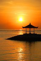 Breathtaking sunrise over the ocean, silhouetting a sea pagoda in Bali, Indonesia.