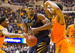 West Virginia Mountaineers forward Jonathan Holton (1) is fouled against the Oklahoma State Cowboys during the first half at the WVU Coliseum.