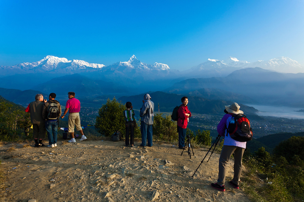 Photographers and tourists look out toward the Annapurna Range, Nepal.