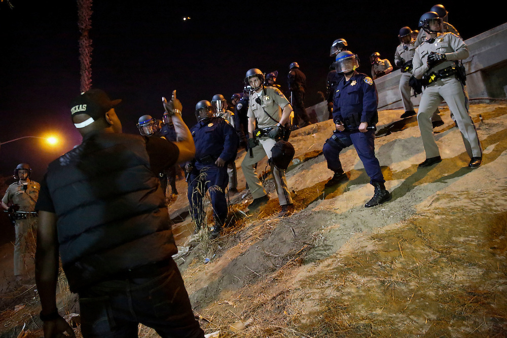 CHP officers make their way down a steep hill in formation while removing protestors blocking the 110 Freeway. People protest the decision of the Ferguson grand jury and the death of Michael Brown on Monday, November 24, 2014 in Los Angeles, Calif. (Patrick T. Fallon/ For the Los Angeles Times)