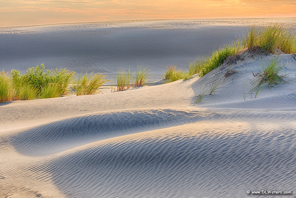 Sand dune on Jockey's Ridge State Park lit by the setting sun  off the reflected clouds.