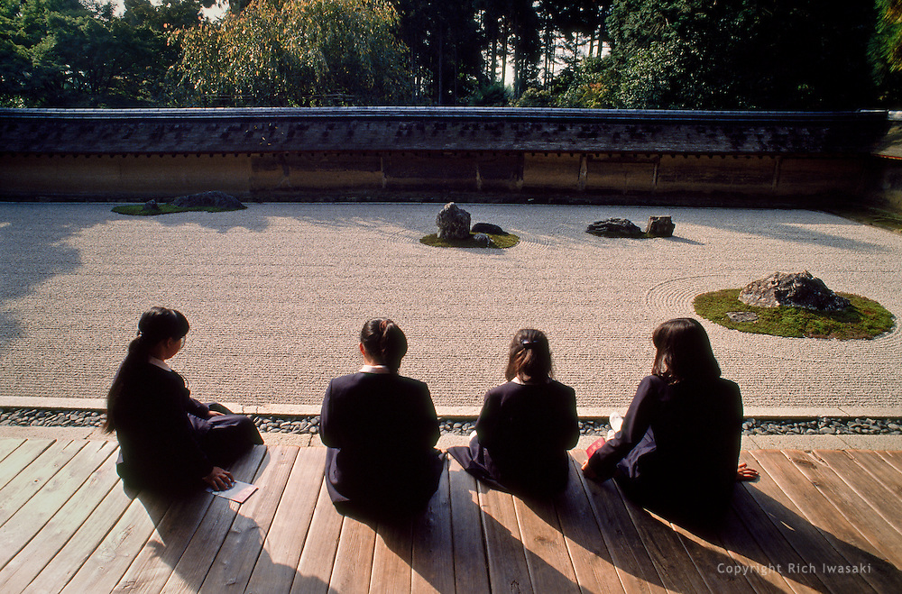Young students contemplate the rock garden at Ryoan-ji (temple), Kyoto, Japan