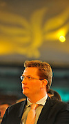 © Licensed to London News Pictures. 20/09/2011. BIRMINGHAM, UK.   Danny Alexander watches Chris Huhne deliver a speech on the climate at the Liberal Democrat Conference at the Birmingham ICC today (20 Sept 2011): Stephen Simpson/LNP . Photo credit : Stephen Simpson/LNP