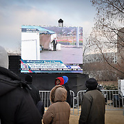 Live news broadcast on the National Mall displays President-elect Obama's movements in Washington, DC on the eve of his inauguration.