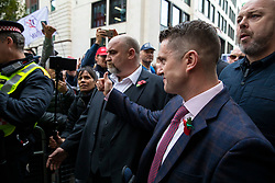 © Licensed to London News Pictures. 23/10/2018. London, UK. Former English Defence League leader Tommy Robinson gives a thumbs-up to a supporter outside the Old Bailey in London, where he is accused of contempt of court for breaking reporting restrictions around the Huddersfield grooming gang trial. Photo credit: Rob Pinney/LNP