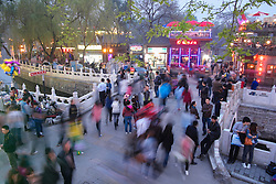 Busy street on historic bridge beside popular tourist location at Houhai Lake in Beijing China