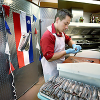 Nederland, Amsterdam Zuid Oost, 6 juni 2011. ,.Hollandse Nieuwe (haring) wordt schoongemaakt door visboer Theo van de Geest en Heidi Talen van Vishandel volendaam op het bijlmerplein.Fishmonger Theo Spirit cleans New herring,  in the fish shop Volendam in Amsterdam.