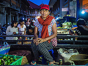 11 OCTOBER 2016 - UBUD, BALI, INDONESIA: A vendor in the market in Ubud. The morning market in Ubud is for produce and meat and serves local people from about 4:30 AM until about 7:30 AM. As the morning progresses the local vendors pack up and leave and vendors selling tourist curios move in. By about 8:30 AM the market is mostly a tourist market selling curios to tourists. Ubud is Bali's art and cultural center.      PHOTO BY JACK KURTZ