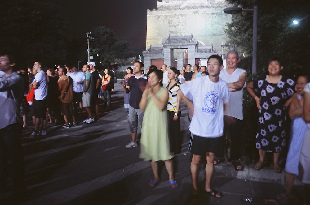 The Olympic Games ceremony from the street<br /> Near the Drum Tower, some Beijingers are looking at fireworks at the end of the opening ceremony of the Olympic Games of Beijing, August 8 2008<br /> High Resolution available