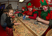 Grace Wooten picks out her special ornament made by Santas elves in their workshop during opening night of the Christmas Village.  (Karen Bobotas/for the Laconia Daily Sun)