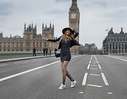 © Licensed to London News Pictures.23/03/2017.London, UK. A French tourist poses for a photograph for her boyfriend as Westminster  Bridge is opened the day after a lone terrorist killed 4 people and injured several more, in an attack using a car and a knife. The attacker managed to gain entry to the grounds of the Houses of Parliament, killing one police officer.Photo credit: Peter Macdiarmid/LNP