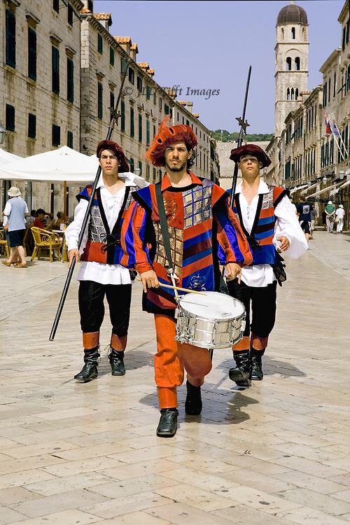 Frontal view of three young men in colorful costume with drum and spears marching down the main street.