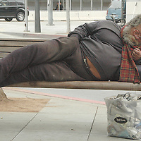 A homeless man sleeps on a bench at the 100 block of Broadway Ave. on Saturday, June 26, 2010.