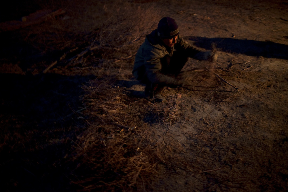 CREDIT: DOMINIC BRACCO II..SLUG:PRJ/KAZAKHSTAN..DATE:10/31/2009..CAPTION:Fisherman Almat Aidoraliev, 21 of Aralsk, breaks up firewood to heat their shelter near the Aral Sea on October 31, 2009...Aral Sea Overview: ..During the 1960s the USSR began irrigating the waters of the Aral Sea in southern Kazakhstan to combat their growing food crisis. The Soviets severely miscalculated and water began receding quickly from the port cities. The waters continued to recede. By 2000 the water was 80 km away from the city of Aralsk, a main seaport in Kazakhstan. In 2005 with help from the World Bank, construction began on a 13km dike that locals hoped would bring the waters back to their original shores. The project raised water quality and fishing was able to resume, however four years after completion of the dike the water is still 50km from Aralsk's port. Locals seem mixed on the possibility of the sea returning after more than 40 years without the sea. Fishermen from Aralsk make a three-hour path through soft desert road along the former seabed. The only source of income for many is cattle, horses, and camels, which have, began to overgraze the areas of the former seabed and surrounding desert. Because of this nutrient rich topsoil is lifted by the wind and the process of desertification continues.  .