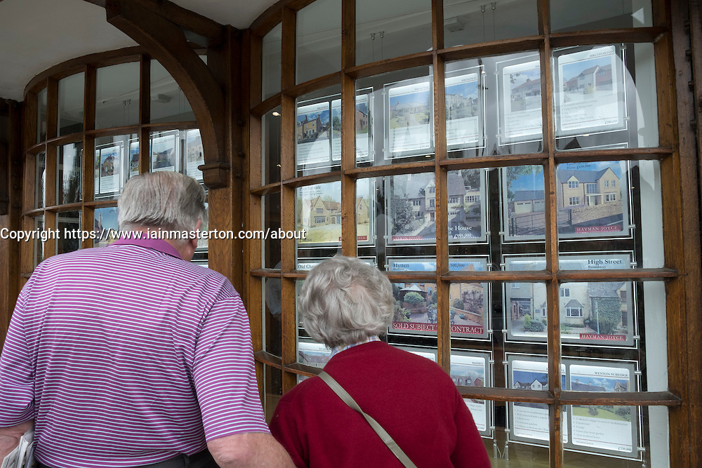 Senior couple looking in estate agents window at property for sale in the Cotswolds in England, United Kingdom
