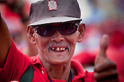 """Mar. 26, 2009 -- BANGKOK, THAILAND: A man missing several teeth cheers for opposition politicians during an anti-government protest in Bangkok. More than 30,000 members of the United Front of Democracy Against Dictatorship (UDD), also known as the """"Red Shirts""""  and their supporters descended on central Bangkok Thursday to protest against and demand the resignation of current Thai Prime Minister Abhisit Vejjajiva and his government. Abhisit was not at Government House Thursday. The protest is a continuation of protests the Red Shirts have been holding across Thailand in March.  Photo by Jack Kurtz"""