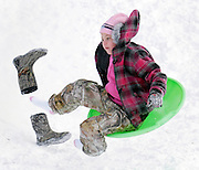 Kelli Rauche loses her boots as she comes off a snow ramp while sledding in Tulsa, OK.