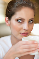 Close-up portrait of a young woman holding coffee cup