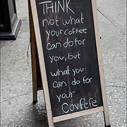 Humorous blackboard sign outside reflecting the sense of humor and attitude of the coffe shop.<br /> <br /> &quot;THINK not what your coffee can do for you, but what you can do for your covfefe&quot;