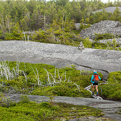 A teenage girl hiking on Moxie Bald Mountain. Moxie Pond is in the distance. Appalachian Trail. Bald Mountain Township, Maine.