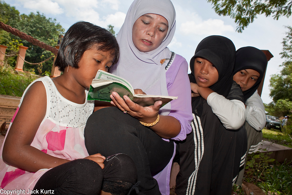 "Sept 27, 2009 -- BACHO, NARATHIWAT: SINA YUNUH and her daughter pray at a mass grave near the 300 Year Mosque in Bacho, Narathiwat, Thailand, for 22 Muslim men killed by Thai security forces in Oct. 2004. She said she believes her husband is buried here, but that his body was unidentifiable because of the mutilation. According to local community leaders, many of the men in the grave are unidentified because the bodies were mutilated beyond recognition before they were returned to their families.  Thailand's three southern most provinces; Yala, Pattani and Narathiwat are often called ""restive"" and a decades long Muslim insurgency has gained traction recently. Nearly 4,000 people have been killed since 2004. The three southern provinces are under emergency control and there are more than 60,000 Thai military, police and paramilitary militia forces trying to keep the peace battling insurgents who favor car bombs and assassination.   Photo by Jack Kurtz / ZUMA Press"