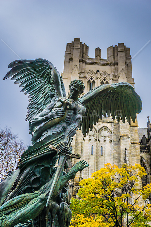 The Peace Fountain is a 1985 sculpture and fountain located next to the Cathedral of Saint John the Divine in the Morningside Heights section of New York City by Greg Wyatt, sculptor-in-residence at the Cathedral. The sculpture depicts the struggle of good and evil, as well as a battle between the Archangel Michael and Satan. The sculpture also contains the Sun, the Moon, and several animals. Although it is called a fountain, there is currently no water on the site. A plaque at the base contains the following inscription:<br /> <br /> Peace Fountain celebrates the triumph of Good over Evil, and sets before us the world's opposing forces—violence and harmony, light and darkness, life and death—which God reconciles in his peace.When the fountain operates, four courses of water cascade down the freedom pedestal into a maelstrom evoking the primordial chaos of Earth. Foursquare around the base, flames of freedom rise in witness to the future. Ascending from the pool, the freedom pedestal is shaped like the double helix of DNA, the key molecule of life. Atop the pedestal a giant crab reminds us of life's origins in sea and struggle. Facing West, a somnolent Moon reflects tranquility from a joyous Sun smiling to the East. The swirls encircling the heavenly bodies bespeak the larger movements of the cosmos with which earthly life is continuous.
