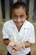 A girl holds two US quarters at the primary school in the town of Coyolito, Honduras on Wednesday April 24, 2013.