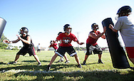Rusty Johnson (from left), 14, freshman, Skyler Matthias, 16, junior, and Tyler Oberhauser, 16, junior, block during a play on the first day of football practice at Central City High School in Central City on Wednesday afternoon, August 3, 2011.
