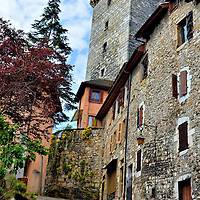 L'Impasse du Trippoz in Annecy, France<br /> Most tourists in Annecy spend their time strolling on the quays along the canals in the center of Old Town. Few people venture onto cobblestone walkways such as L'Impasse du Trippoz at the base of the Château d'Annecy tower. If you get lost, just ask the black cat on the left for directions.