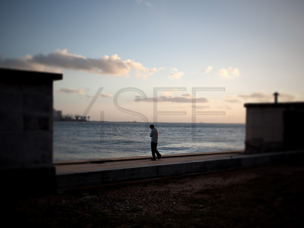 A man stands in the border of river Tejo (Tagus), next to the Tower of Belém.This photograph is part of a body of work about Lisbon, feelings, affections and loneliness. Is about a city depressed by the crisis, but even so, tolerant and cosmopolitan. This part of Lisbon, near the river Tejo (Tagus), with his deep character, where local people meets foreigners and alternative ways of life mixes with shamefaced poverty, is sublime by its peculiar light.