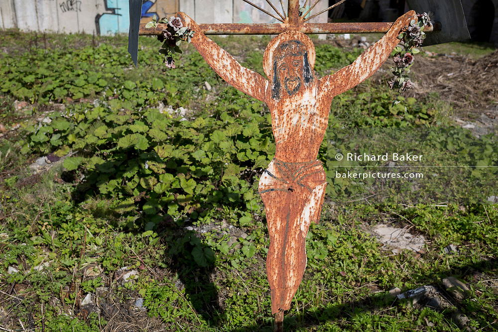 A sheet metal Jesus crucifix (a popular local copy from an historical Rutherian church) outside an abandoned industrial building on the outskirts of Jaworki, on 20th September 2019, <br /> near Szczawnica, Malopolska, Poland. The village of a thriving Rutherian community was once in nearby Biala Woda where over 100 farms were located - the remains of which are still seen. A wooden cross with a figure of Christ cut from sheet metal survived the culture. Similar crosses and chapels can be found in the colloquial language of White Water  in the Romanian, Ukrainian or Eastern Slovakia Carpathians.
