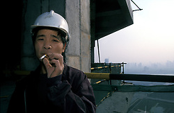 CHINA SHANGHAI PUDONG MAY99 - A Chinese construction worker takes a cigarette break on top of a Pudong Highrise construction site. Pudong has experienced a dramatic rise in construction projects, although vacancy rates stand at nearly 60% and a bust-cycle is imminent. ..jre/Photo by Jiri Rezac..© Jiri Rezac 1999..Contact: +44 (0) 7050 110 417.Mobile: +44 (0) 7801 337 683.Office: +44 (0) 20 8968 9635..Email: jiri@jirirezac.com.Web: www.jirirezac.com..© All images Jiri Rezac 1999 - All rights reserved.
