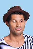 Close-up portrait of young man wearing hat over blue background