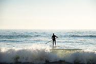Stand Up Paddle Boarder heading out over wave at Terramar Surf Beach in Carlsbad, CA