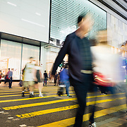 Blurred motion of pedestrians crossing street at nigtht in the shopping district of Tsim Sha Tsui, Hong Kong.