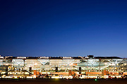 "An wide exterior view of Heathrow Airport's Terminal 5 building in West London. Created by the Richard Rogers Partnership (now Rogers Stirk Harbour and Partners). As the last light of the day fades, the brightness of terminal lights shine through massive panes of window glass. At a cost of £4.3 billion, the 400m long T5 is the largest free-standing building in the UK with the capacity to serve around 30 million passengers a year. The Terminal 5 public inquiry was the longest in UK history, lasting four years from 1995 to 1999. From writer Alain de Botton's book project ""A Week at the Airport: A Heathrow Diary"" (2009). ..."