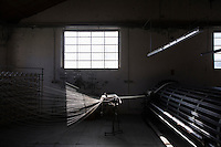 """SOVERIA MANNELLI, ITALY - 17 NOVEMBER 2016: An old warping mill is seen here at the Lanificio Leo woolen mill in Soveria Mannelli, Italy, on November 17th 2016.<br /> <br /> Lanificio Leo was the first and last machine-operated woolen mill of Calabria, founded in 1873, it employed 50 people until the 1970s, when national policies to develop Italy's South cut out small businesses and encouraged larger productions or employment in the public administration.<br /> <br /> The woolen mill was on stand-by for about two decades, until Emilio Salvatore Leo, 41, started inviting international designers and artists to summer residencies in Soveria Mannelli. With their inspiration, he tried to envision a future for his mill and his town that was not of a museum of the past,<br /> Over the years, Mr. Leo transformed his family's industrial converter of Calabrian wool into a brand that makes design products for home and wear. His century old machines now weave wool from Australia or New Zealand, cashmere from Nepal and cotton from Egypt or South America. He calls it a """"start-up on scrap metals,"""" referring to the dozens of different looms that his family acquired over the years.<br /> <br /> Soveria Mannelli is a mountain-top village in the southern region of Calabria that counts 3,070 inhabitants. The town was a strategic outpost until the 1970s, when the main artery road from Naples area to Italy's south-western tip, Reggio Calabria went through the town. But once the government started building a motorway miles away, it was cut out from the fastest communications and from the most ambitious plans to develop Italy's South. Instead of despairing, residents benefited of the geographical disadvantage to keep away the mafia infiltrations, and started creating solid businesses thanks to its administrative stability, its forward-thinking mayors and a vibrant entrepreneurship numbering a national, medium-sized publishing house, a leading school furniture manufacturer and an ancient wo"""