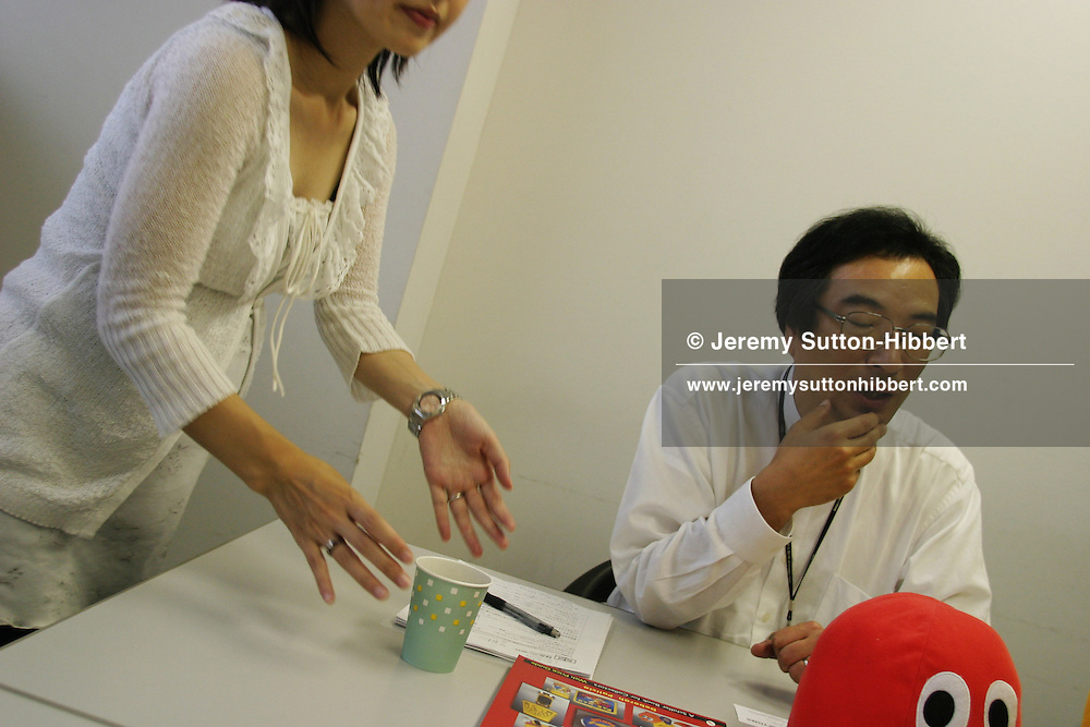 An employee places a drink on the table for Toru Iwatani, game designer for Namco, and designer/inventor of Pac-Man, during an interview in Tokyo, Japan, on Friday, July 1st 2005.  During interviews it is common for female assistants to enter the rooms silently , bringing refreshment drinks of green tea, coffee, or orange juice, to the company head and his guests.