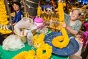 19 OCTOBER 2012 - BANGKOK, THAILAND:  A vendor makes a marigold garland in the Bangkok Flower Market. The Bangkok Flower Market (Pak Klong Talad) is the biggest wholesale and retail fresh flower market in Bangkok.  The market is busiest between 3:30AM and 6AM. Thais grow and use a lot of flowers. Some, like marigolds and lotus, are used for religious purposes. Others are purely ornamental.          PHOTO BY JACK KURTZ