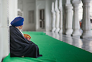 Sikh man with turban sitting and resting at Golden Temple in Amritsar (India)