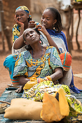 3 June 2019, Djohong, Cameroon: 15-year-old Adija (right) braids her mother Didi's (centre) hair by their home in the Borgop refugee camp. Adija says she has been braiding hair since she was 13 years old, and today knows more than ten different types of braids. The end of Ramadan is drawing near, so people in the mostly Muslim Borgop refugee camp are decorating themselves in preparation for celebrations of the end of the annual period of fasting. The Borgop refugee camp is located in the municipality of Djohong, in the Mbere subdivision of the Adamaoua regional state in Cameroon. Supported by the Lutheran World Federation since 2015, the camp currently holds 12,300 refugees from the Central African Republic.