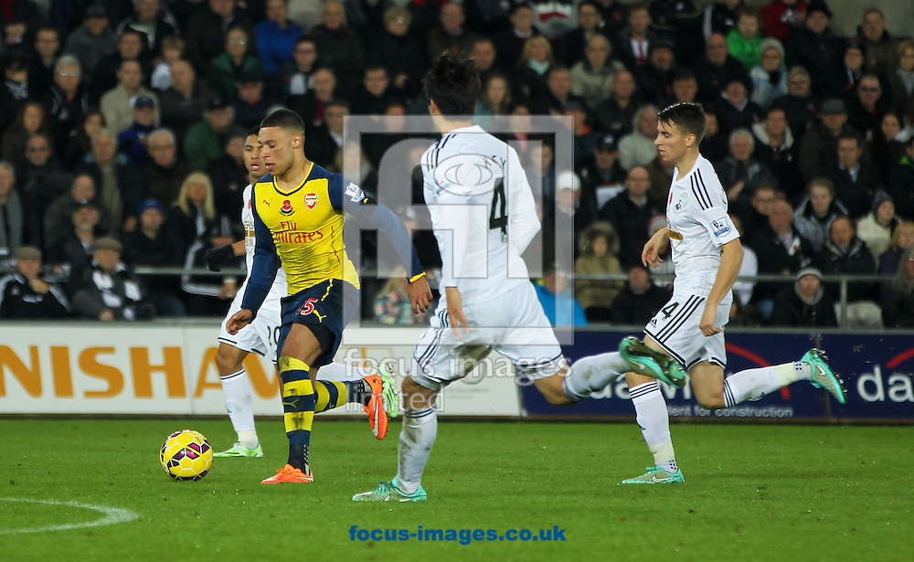 Alex Oxlade-Chamberlain (2nd left) of Arsenal takes the ball forward during the Barclays Premier League match at the Liberty Stadium, Swansea<br /> Picture by Tom Smith/Focus Images Ltd 07545141164<br /> 09/11/2014