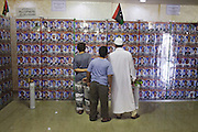 A family in the Misrata war memorial museum watch the wall of martyrs where the pictures of about 2000 persons killed during the civil war are exposed.