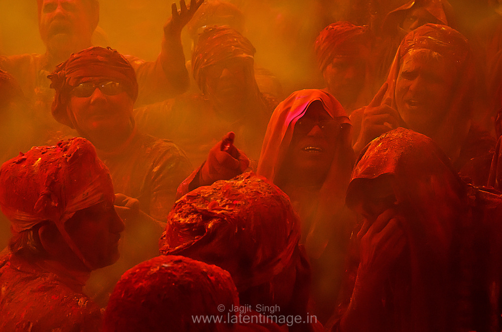 Samaj at Radha Rani temple, Barsana. People sing loudly in a very colorful environment. Dry and wet colors splashed on them from all corners of the temple. Braj ki Holi