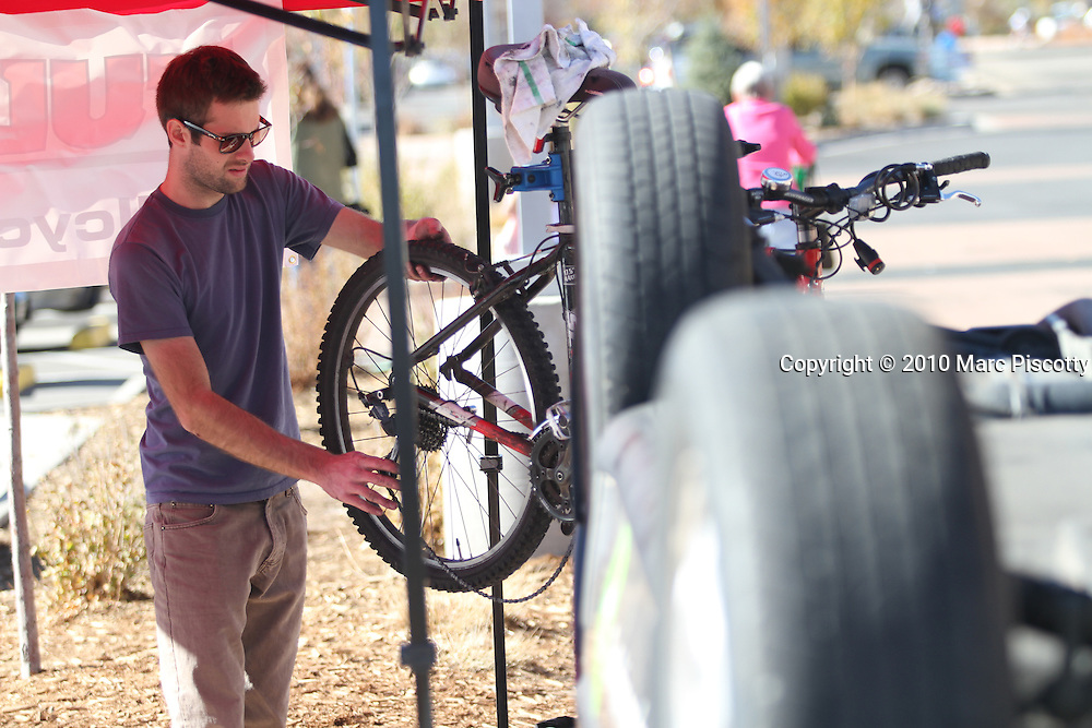 SHOT 11/6/10 12:25:19 PM - Members of Driven to Drive Less display a car turned upside down and offer free bike tunes and maintenance in front of the Whole Foods grocery store in Boulder, Co. on Saturday November 7, 2010. Driven to Drive Less is a program being undertaken by the city of Boulder, Co. that encourages participants to stimulate long term travel behavior change and to creatively demonstrate to the general public the ability of Boulder residents to live car free or car lite. Participants receive benefits and discounts at local stores for pledging to give up driving their vehicle one day a week. (Photo by Marc Piscotty / © 2010)