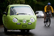 A green electric car known as the Xebra, manufactured by the Zap corporation on the road next to a bike, in Bend, Oregon.  The ZAP motor company stands for Zero Air Pollution, and manufactures and distributes it vehicles through auto dealers in the USA.