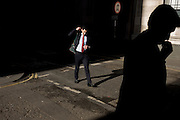 Man adjusting his bag walks through a shaft of early spring light in a side street in the capital's financial district. This is Lombard Street, originally a piece of land granted by King Edward I to goldsmiths from the part of northern Italy known as Lombardy (larger than the modern region of Lombardy). It is a narrow and usually dark sidestreet near the Bank of England in the heart of what is called the Square Mile - the inner-part and oldest quarter of London occupied first by the Romans 2,000 years ago. Nowadays the City of London is home to banks and financial institutions but also with a resident population of under 10,000 but a daily working population of 311,000.